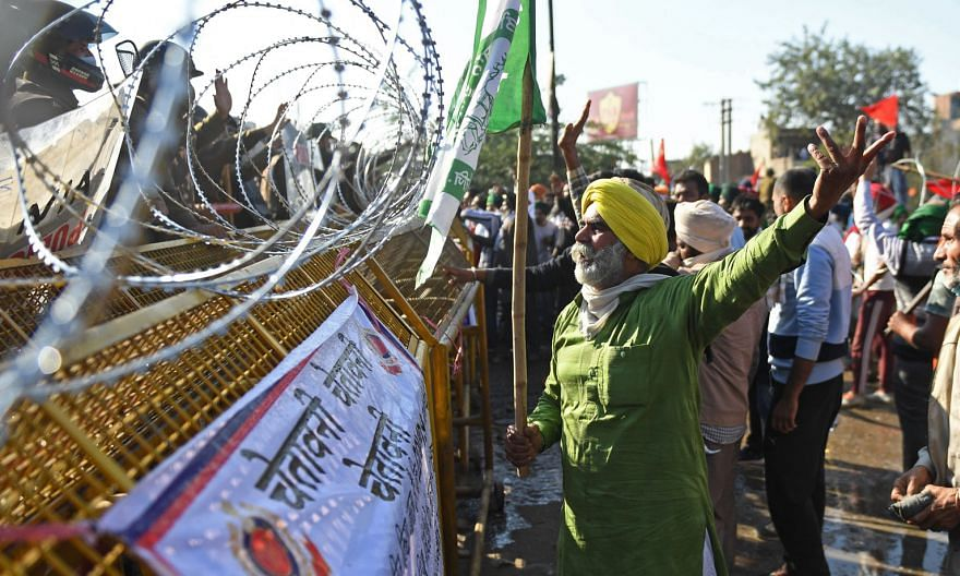 Farmers reacting to a road barricade set up to prevent them from marching into New Delhi yesterday at the Delhi-Haryana border. They were demanding a repeal of new laws liberalising procurement of agricultural produce.