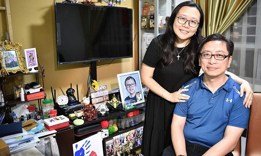 Raphael's parents, Mr William Lee, 47, a course manager with St John Singapore, and Mrs Winnie Lee, 45, a former childcare teacher who left her job last year to look after her son, beside the TV console that's crowded with Raphael's belongings. The b