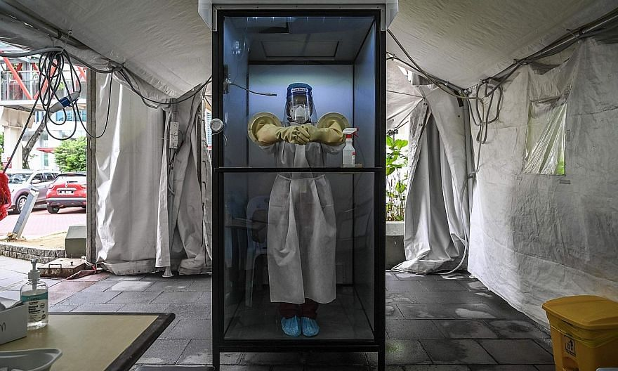 A health worker in a non-contact chamber used to take Covid-19 swab samples at a medical centre in Selangor. The Malaysian government is to conduct Covid-19 tests on 1.7 million foreign workers in the country. PHOTO: AGENCE FRANCE-PRESSE