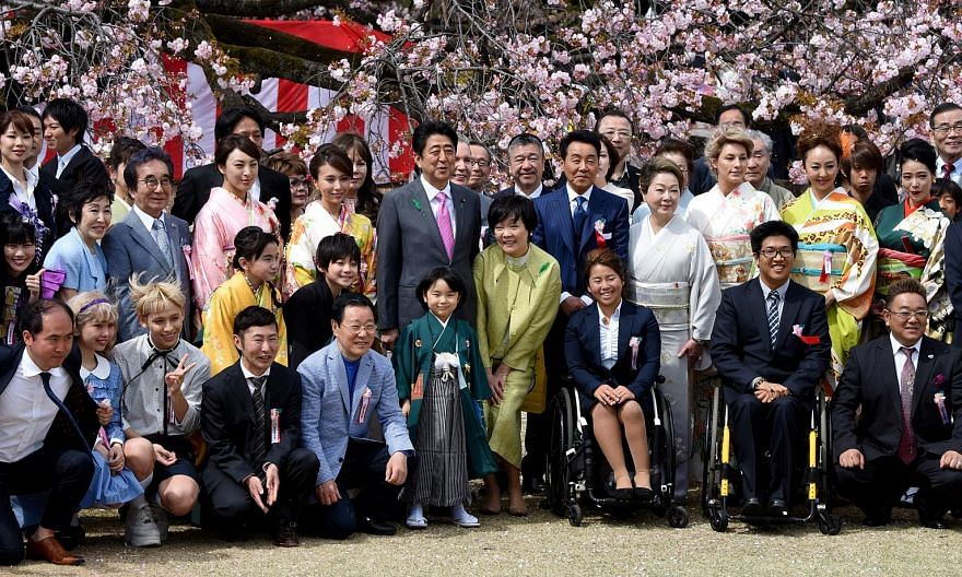 Mr Shinzo Abe and his wife Akie (both centre) posing with entertainers and athletes during a cherry blossom viewing party hosted by the then Prime Minister in Tokyo in April 2017.