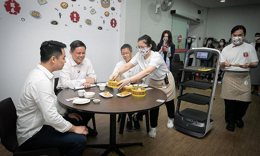 Minister for Trade and Industry Chan Chun Sing having dim sum with Swee Choon Tim Sum Restaurant's third-generation owner Ernest Ting (far left) and second-generation owner Tony Ting during a visit to the eatery yesterday. Mr Chan cited Swee Choon as