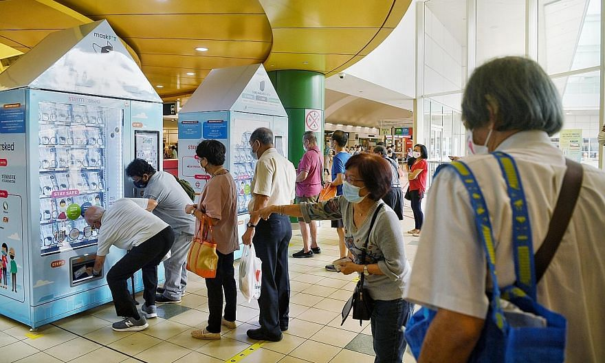 People collecting new reusable face masks at a vending machine in the Toa Payoh Bus Interchange on the first day of distribution by Temasek Foundation yesterday. Each person is entitled to one free mask kit, which contains a pair of reusable masks an