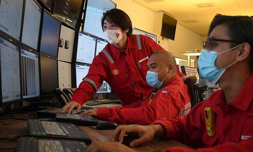 Team leader Lee Xue Ling (standing) with technicians at a control room in Shell's Pulau Bukom refinery yesterday. Ms Lee is one of the potential beneficiaries of the Joint Capability Council, which, in the first phase, will offer training programmes