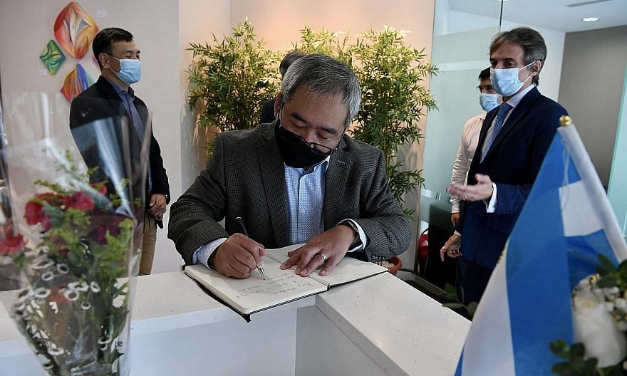 SRU vice-president David Lim signing the condolence book at the embassy as Argentinian ambassador Federico Barttfeld looks on. On the left is SRU president Terence Khoo.