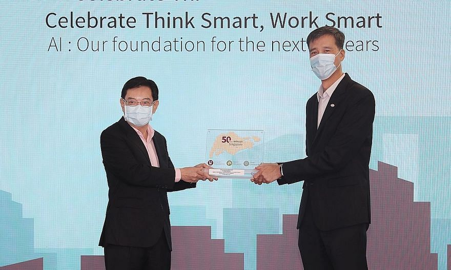 Deputy Prime Minister Heng Swee Keat receiving a plaque from Infineon Technologies Asia Pacific president and managing director Chua Chee Seong yesterday, at a ceremony to mark the company's 50th year in Singapore. Mr Heng said Infineon is a role mod