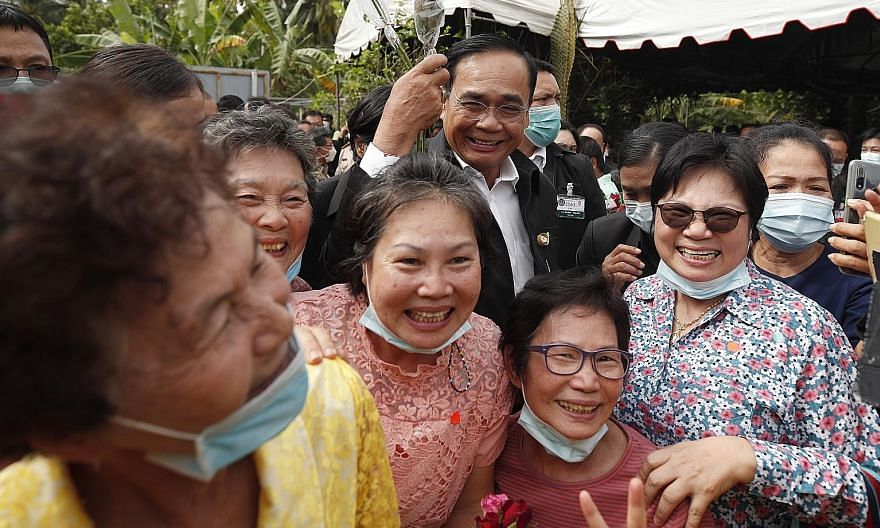 Prime Minister Prayut Chan-o-cha with villagers during a visit yesterday to Samut Songkhram province. He retired as army chief in 2014 but he and his family have continued to stay in the army quarters for security reasons.