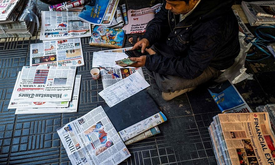 A newspaper vendor in New Delhi. Many Indian papers and websites carry syndicated articles from international publications such as The New York Times, The Wall Street Journal and The Economist.