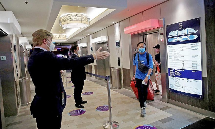 Quantum of the Seas staff directing passengers as they exited elevators on the cruise ship to head towards the Marina Bay Cruise Centre for disembarkation yesterday. All 1,680 passengers and 1,148 crew members disembarked last night.