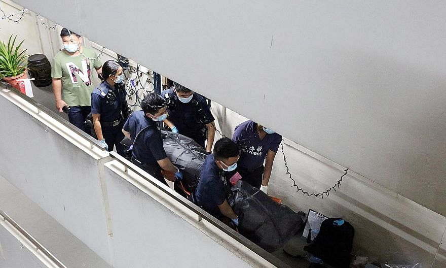 The bodies being removed from the flat in Ho Ching Road on Thursday. Police were alerted to the unnatural deaths at about 4.15pm that day.