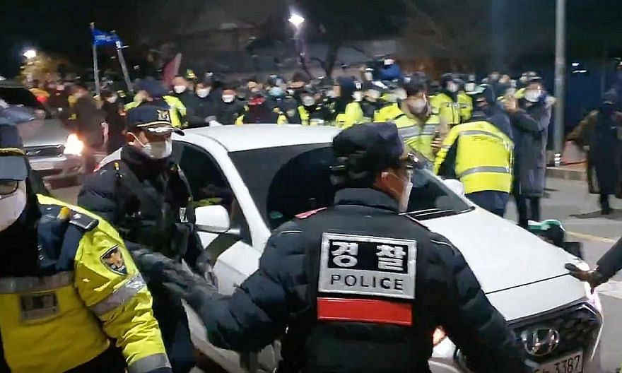 Top: Police officers holding back an angry crowd as Cho Doo-soon arrived at his home in Ansan, South Korea, yesterday. Above: Cho now has to wear a monitoring device for seven years. PHOTOS: SCREENGRABS /TWITTER