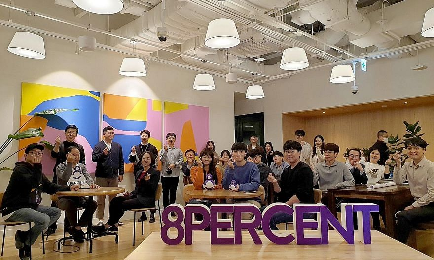 Ms Lee Hyo-jin (seated, third from left), the founder of 8percent, with her employees at an event last month marking the company's sixth anniversary. The peer-to-peer lending start-up matches lenders with cash-strapped individuals or companies by med