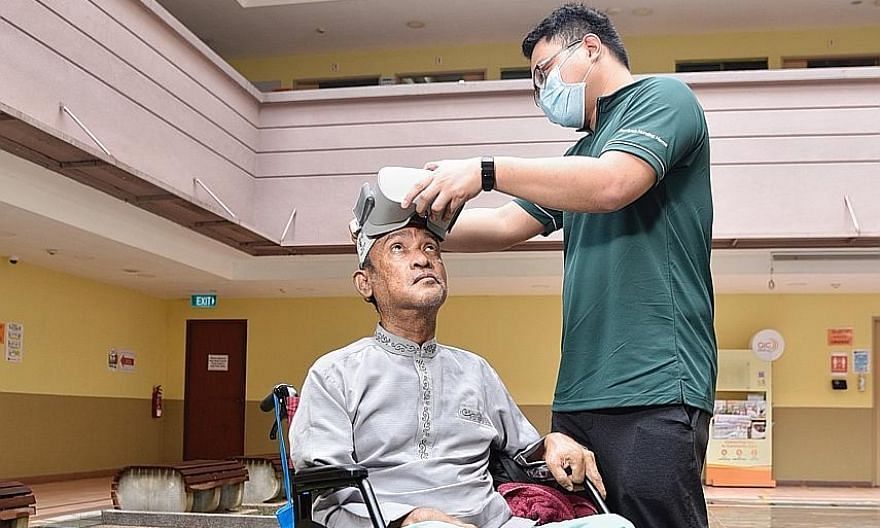Jamiyah Nursing Home therapy assistant Mark Bartolome adjusting a virtual reality headset for Mr Abdul Rahim Abdullah, 64, a resident at the home whose mobility was affected by a stroke. Through the headset, Mr Rahim is able to go on a virtual trisha