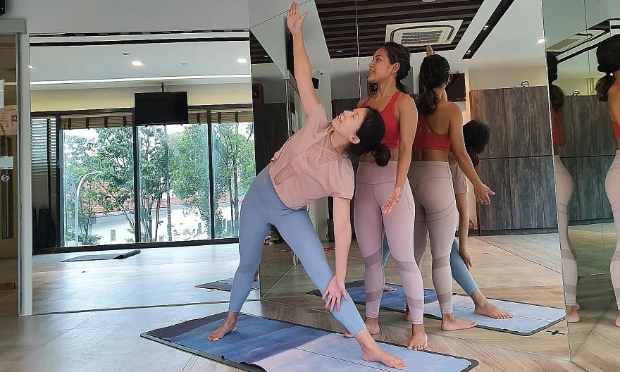 A morning mindfulness class at Tampines Changkat Butterfly Garden led by Brahm Centre chief executive officer and principal Angie Chew (centre). Yoga instructor Danielle Hajar guiding a student.