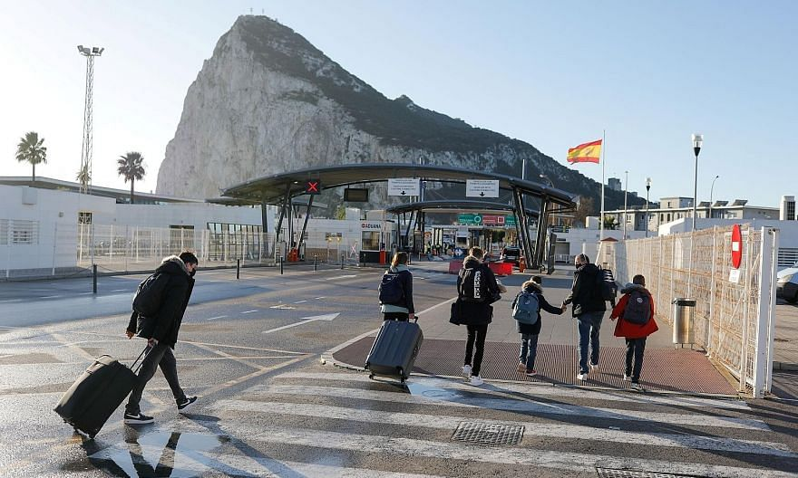 A British family crossing the border from Spain to the British Overseas Territory of Gibraltar in the Spanish city of La Linea de la Concepcion yesterday. Without the agreement reached to keep the land border open, tens of thousands of Spaniards and