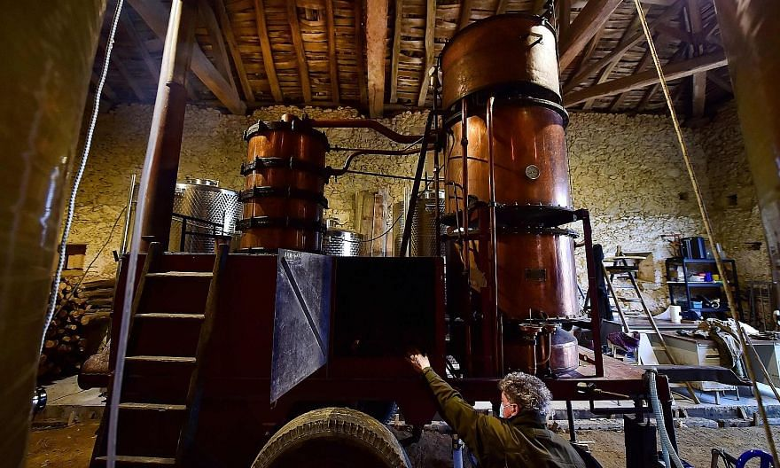 THREE GENERATIONS OF DISTILLERS: Mr Marc Saint-Martin at his old still installed in the cellar of Domaine de Tauriac in Seailles near Vic-Fezensac, in the south-west of France, last month. The Saint-Martin family have been itinerant distillers for th