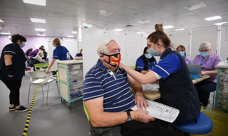 A man receiving a Covid-19 vaccine in Britain on Monday. With the vaccine roll-out gathering steam, some of the funds have been rotating to medium-term winners, recovery plays and growth stocks. PHOTO: BLOOMBERG