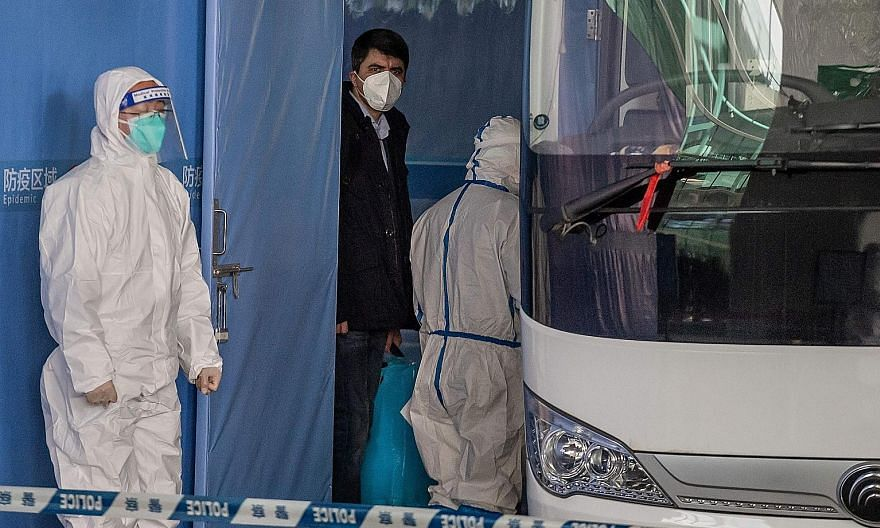 """World Health Organisation Covid-19 investigation team member Vladimir G. Dedkov (centre) about to board a bus after the delegation's arrival in Wuhan yesterday. The team had left the Wuhan airport terminal through a plastic quarantine tunnel marked """""""
