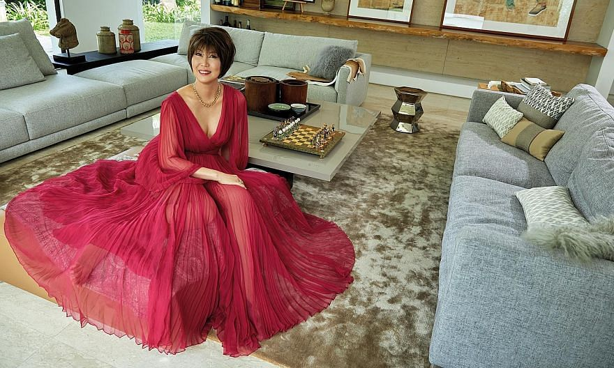 Dr June Goh-Rin wearing a Dior dress and necklace in her living room.