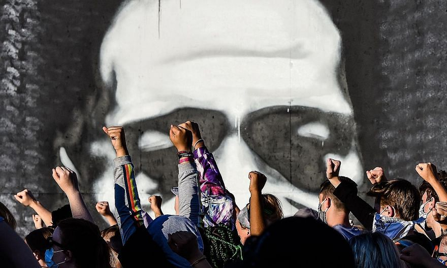 People raising their fists while protesting at the makeshift memorial in honour of Mr George Floyd on June 4 last year in Minneapolis, Minnesota. On May 25 that year, the 46-year-old black man suspected of passing a counterfeit bill died in Minneapol