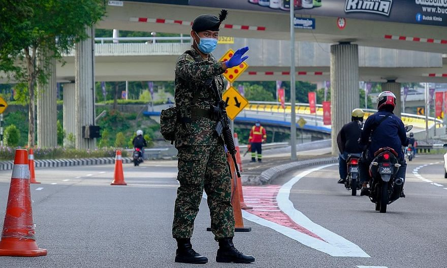 A soldier at a checkpoint in Kuala Lumpur on Wednesday. A surge in new coronavirus cases yesterday saw Malaysia extending its stringent movement controls to a sixth state, Kelantan. PHOTO: BLOOMBERG