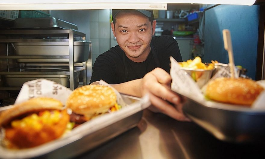 Responding to customers' feedback, Mr Fabian Tan changed his menu four times during the first four months of operations at his burger stall Mr Sheik Mohammad with a plate of his bestseller, the combo platter dulang ($30) that has a bit of everything