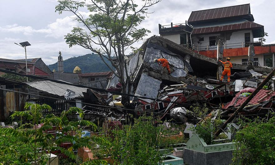Rescue workers inspecting a collapsed building yesterday in Mamuju city, Indonesia's West Sulawesi province, after the earthquake struck on Friday. Among the buildings flattened in the quake was a hospital that collapsed with more than a dozen patien