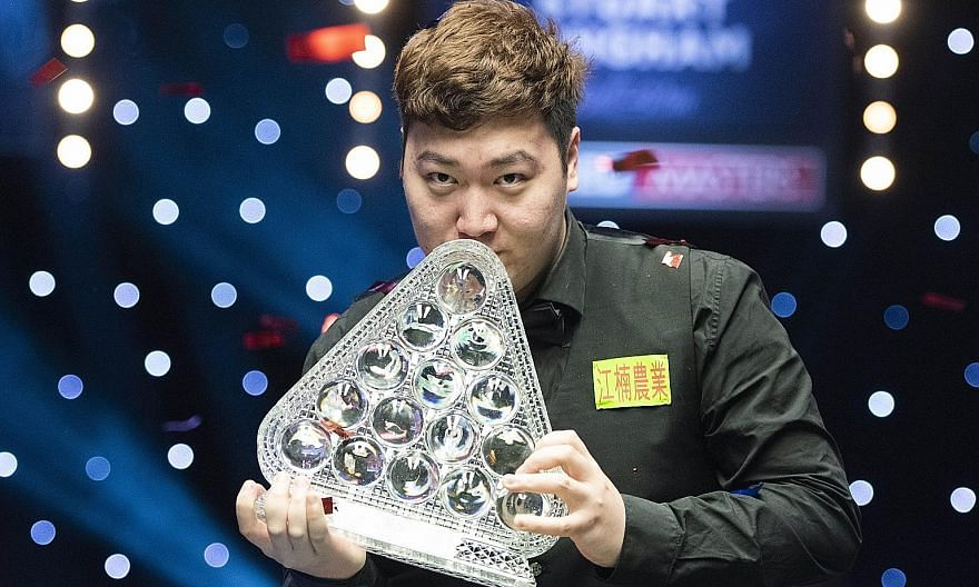 China's Yan Bingtao celebrates by kissing his trophy after beating four-time world champion John Higgins to claim the Masters title in his debut. The 20-year-old is the youngest player in 26 years to win the prestigious snooker tournament.