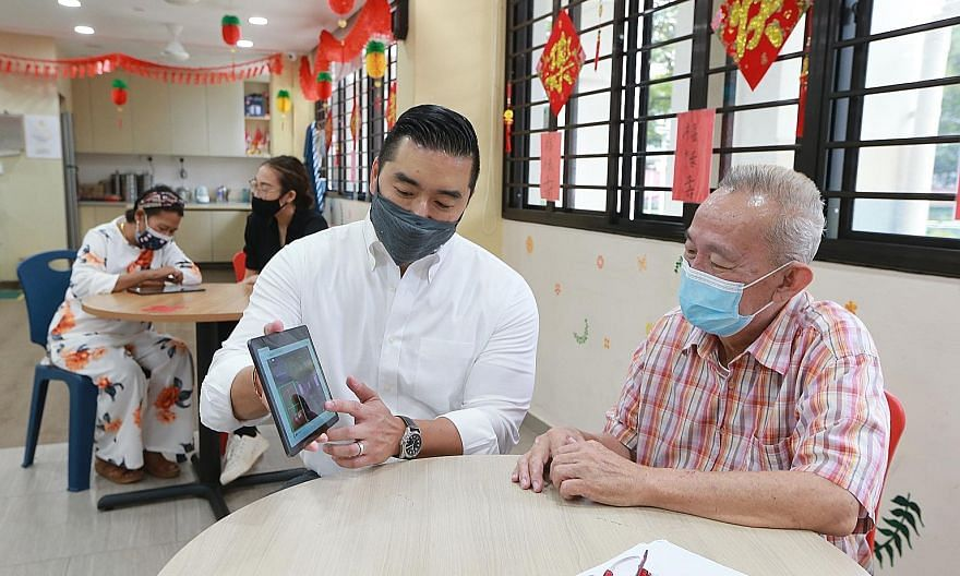 Professor Dean Ho from Yong Loo Lin School of Medicine's Institute for Digital Medicine explaining the game to Mr Lee Keng Wee, 70, at the Sunlove Marsiling Senior Activity Centre yesterday.