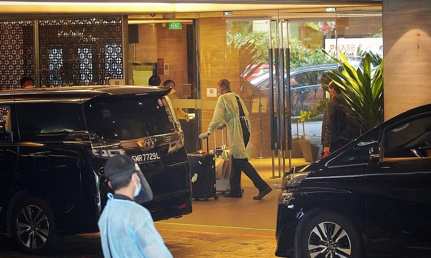 Staff in personal protective equipment moving luggage as guests leave the Mandarin Orchard Singapore hotel on Dec 20 last year. All guests, including local guests on staycation at the hotel's other wing, were moved out as the authorities investigated