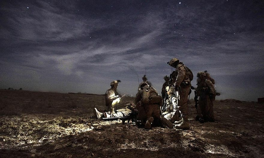 US Marines tending to a comrade injured by an improvised explosive device in Afghanistan in 2010. More than 2,400 Americans have died in the two-decade long war.