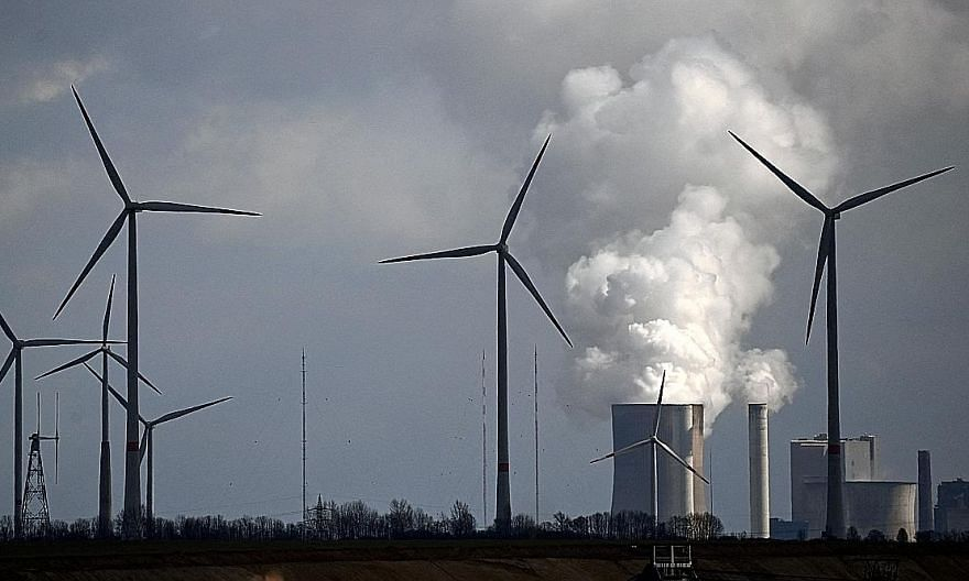 Wind turbines near a coal-fired power station in Germany. Outright carbon emissions, energy consumption and carbon intensity metrics are among the most popular metrics adopted by companies.