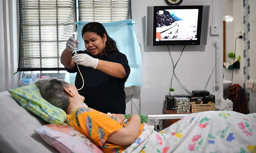 Foreign domestic worker Padua Mae Zate, 37, attending to Ms Mary Teo, 74, who is diabetic, has Parkinson's disease and is bedridden. ST PHOTO: LIM YAOHUI
