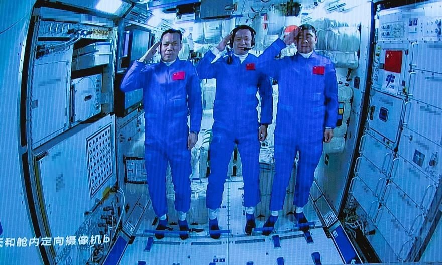 Astronauts (pictured from left) Tang Hongbo, 45, Nie Haisheng, 56, and Liu Boming, 54, saluting after boarding Tianhe, an orbiting module that is the first and largest part of China's Tiangong space station. Mr Liu, like Mr Nie, was from the first ba