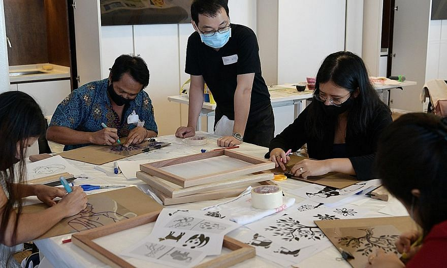 Members of the Myanmar diaspora printing designs on tote bags as part of a National Gallery Singapore tour on Sunday. The tour, which is part of the gallery's Art For Us programme, brought 12 members of the diaspora to view artworks by Myanmar artist