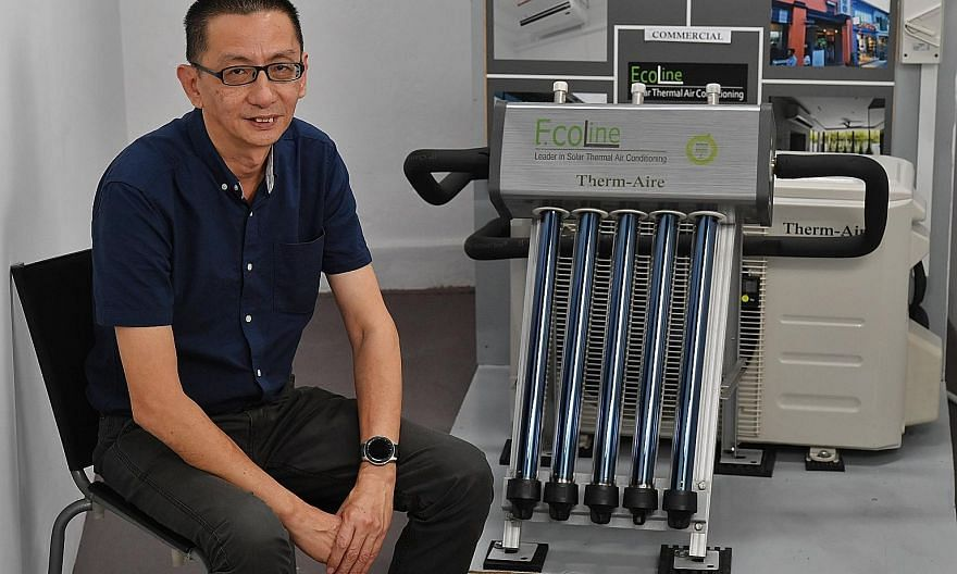 Mr Colin Chia, co-founder of Ecoline Solar, with the solar thermal air-conditioning system manufactured by his firm. ST PHOTO: CHONG JUN LIANG