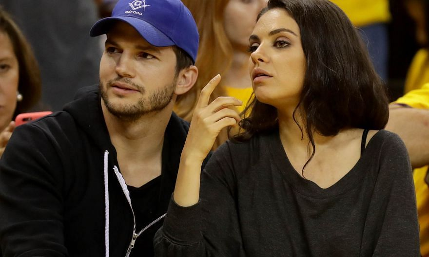 Actor Ashton Kutcher (above, with his wife, actress Mila Kunis) sports a cap while watching a basketball match in June in California.