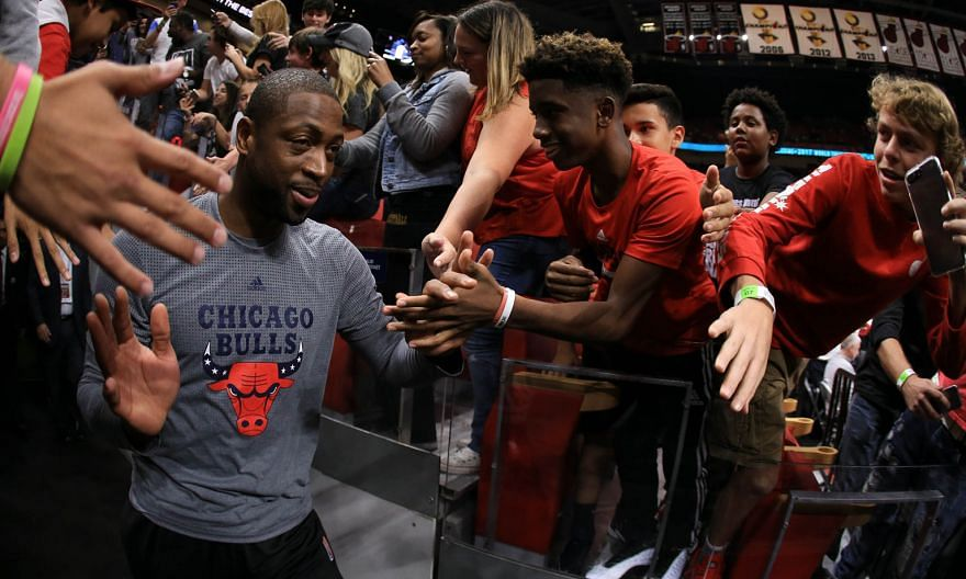 From left: Bulls star Dwyane Wade taking to the court at AmericanAirlines Arena before the game against the Miami Heat. Wade shoots around Heat centre Willie Reed in the first quarter. Wade finished with 13 points, seven rebounds and four assists. Ji