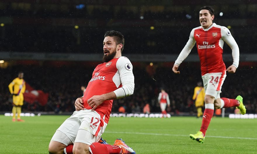 Olivier Giroud, who later said luck played a big part in his audacious goal, basks in the Arsenal fans' cheers as Hector Bellerin rushes to join in.
