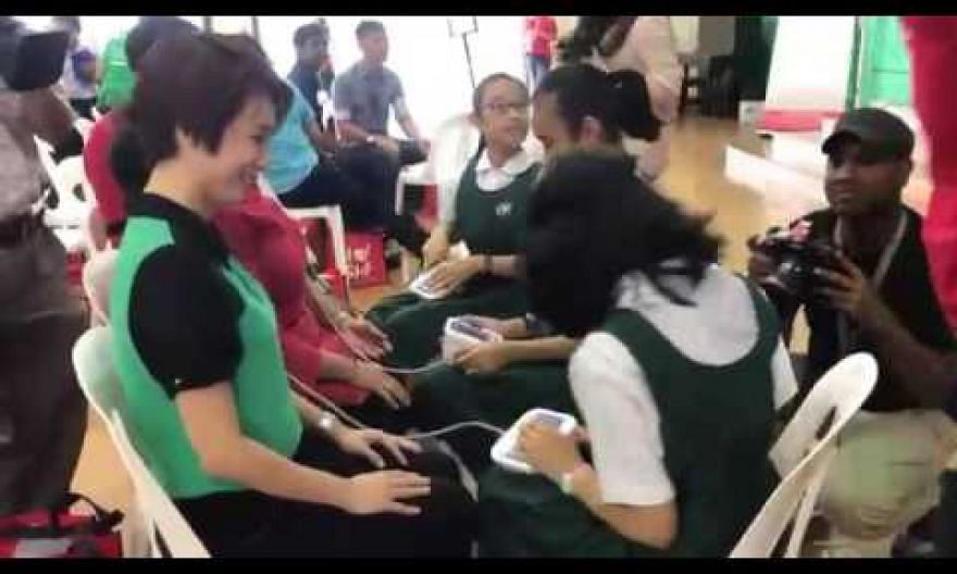 Guest-of-honour Low Yen Ling getting her blood pressure measured by pupils at Juying Primary Sch