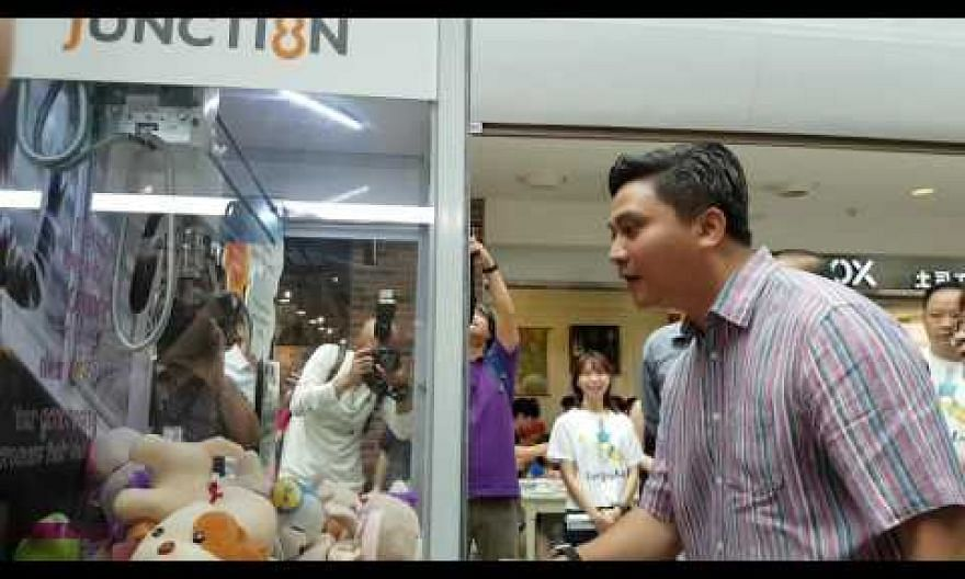 Mr Saktiandi Supaat uses the claw machine at the Thye Hua Kwan Moral Society's roadshow
