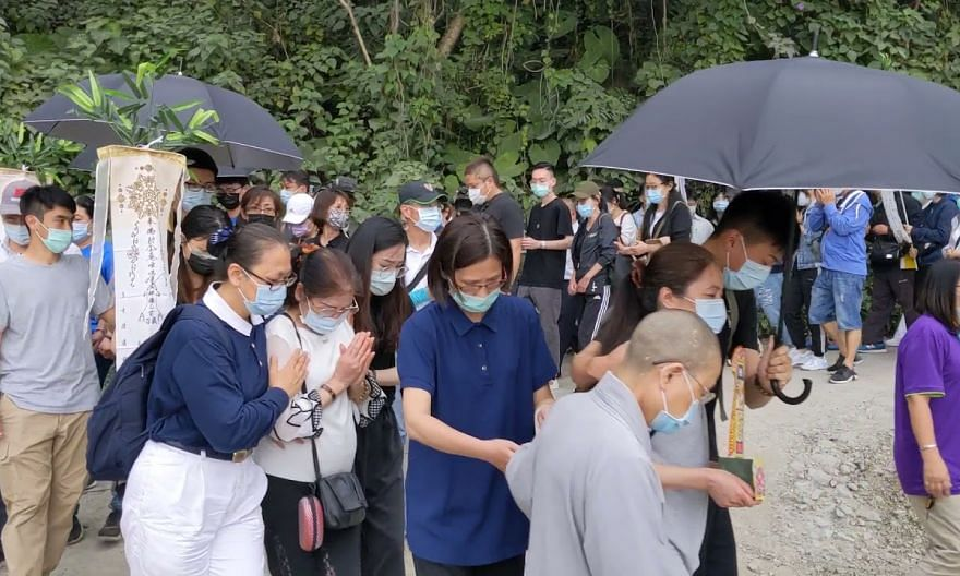 Buddhist volunteers and nuns help grieving family members to the site of the train crash