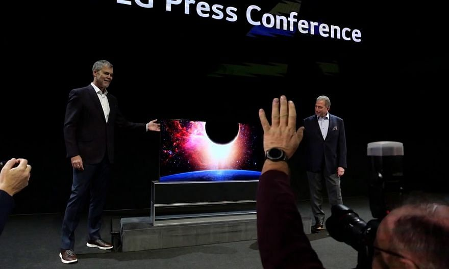 LG's David VanderWaal and Tim Alessi showing off the Signature Oled TV R rollable TV