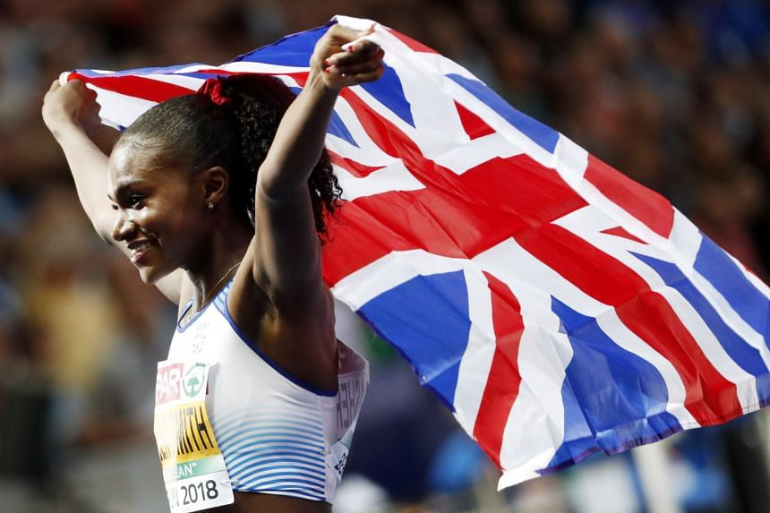 Dina Asher-Smith celebrates after winning the women's 200 final.