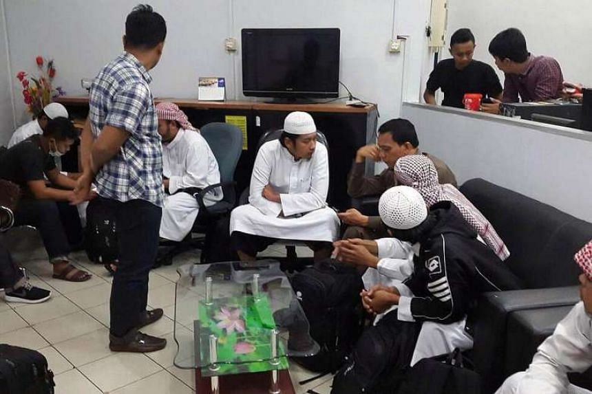Five of the eight deported men (wearing headgear and white robes) being questioned by the Indonesian authorities in the Riau Islands on Jan 10, 2017.