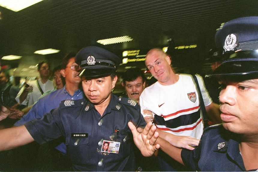 Nick Leeson being escorted by police at Changi Airport after his release from prison in July 1999.