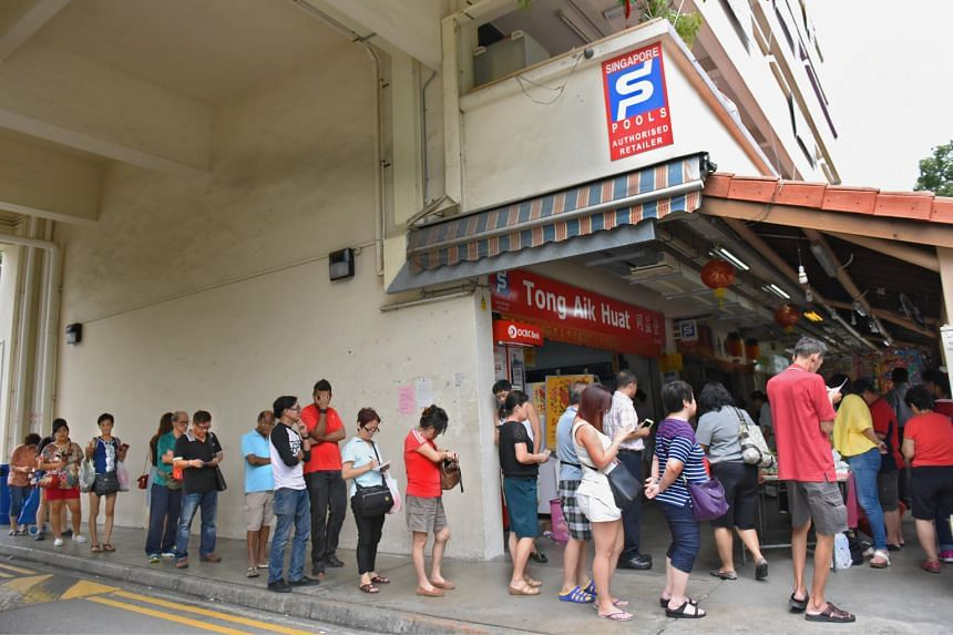 A line of hopeful punters queuing for their turn at the jackpot at Hougang Block 211 on Feb 9, 2017.