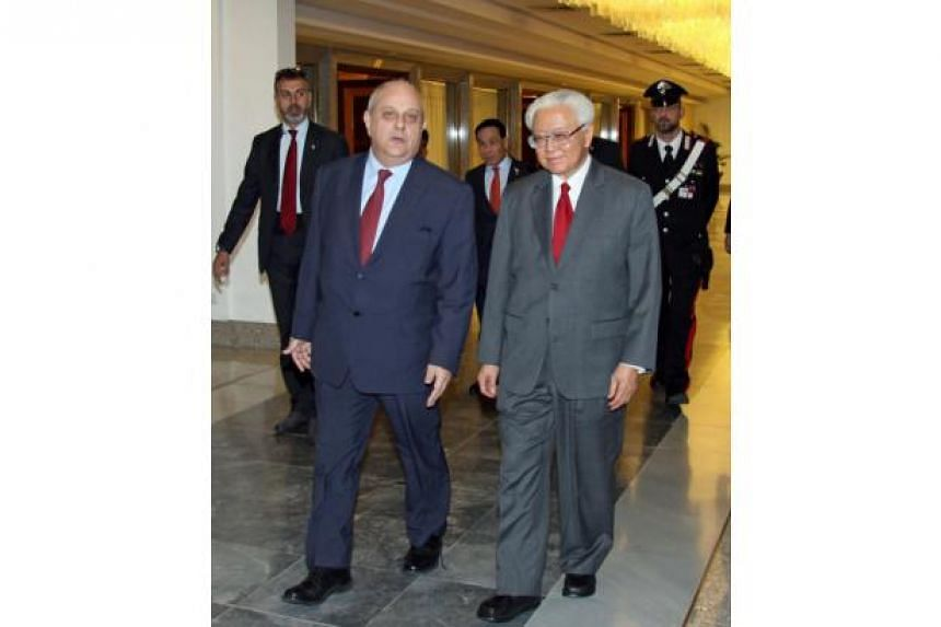 Singapore's President Tony Tan Keng Yam (right) is welcomed by Italian Deputy Foreign Minister Mario Giro (left) upon his arrival at Rome's Fiumicino Airport on May 22, 2016.