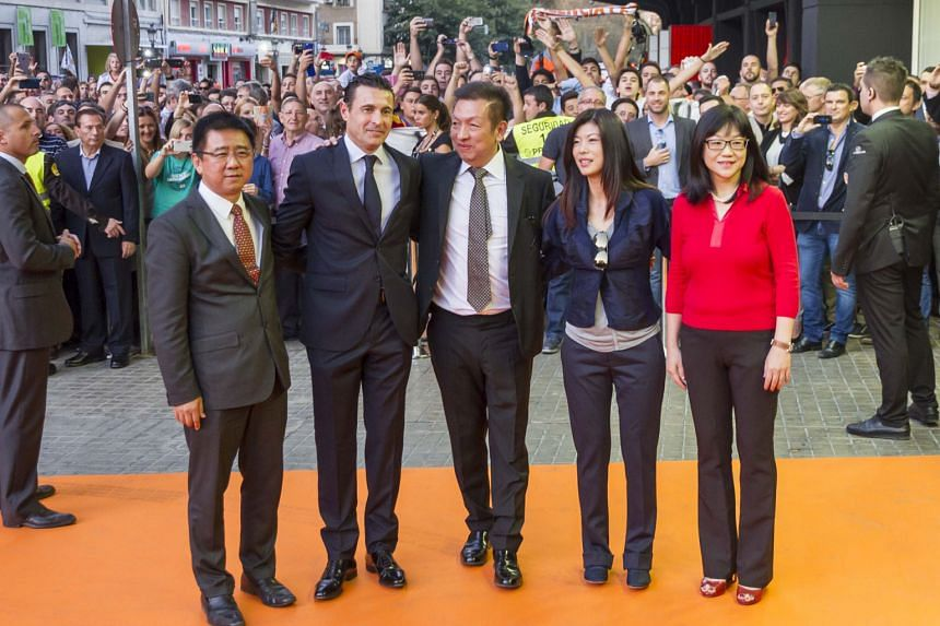 Chan Lay Hoon (right) has come out to defend Valencia club owner Peter Lim (centre) over the latter's sacking of Gary Neville after  just four months on the job.