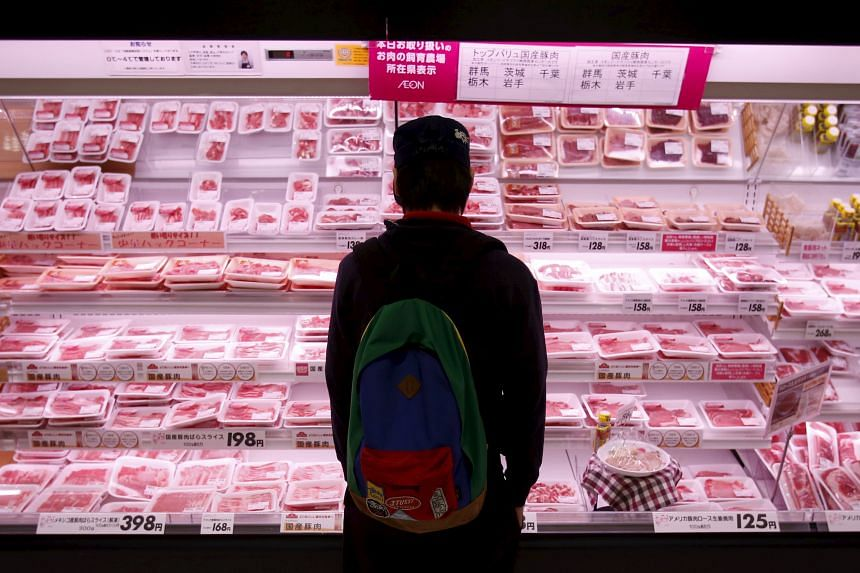 A man browsing meat products at a supermarket in Chiba, Japan. Travellers returning to Singapore from Japan can now bring home beef and pork products with less hassle.
