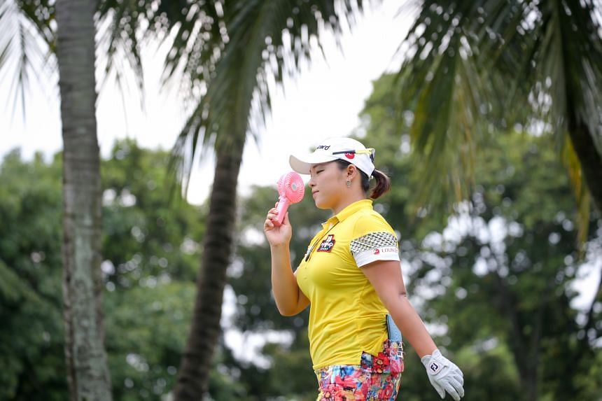 Other golfers found innovative ways to tackle the heat. Jang Ha Na's portable pink fan was just as important as her clubs.